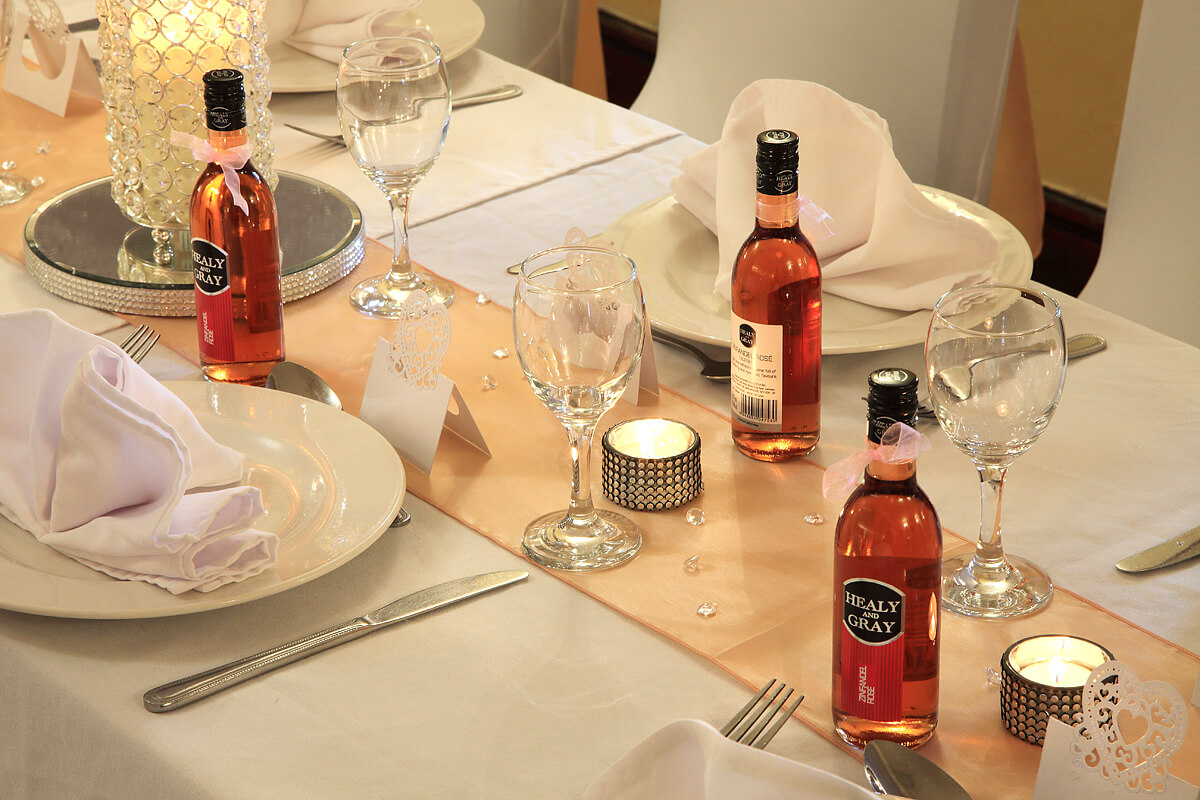 Wedding breakfast table setting with tealights and single serve wine bottles